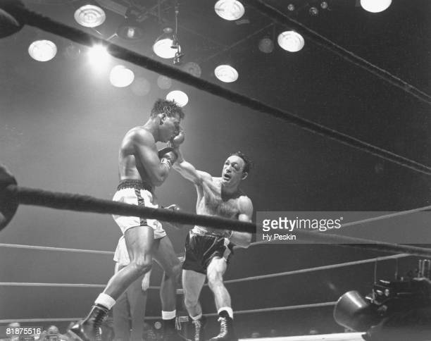 Boxing World Middleweight Title Carmen Basilio with swollen eye injury in action throwing punch vs Sugar Ray Robinson at Chicago Stadium Chicago IL...