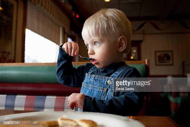 Boy 1-3 eating in diner