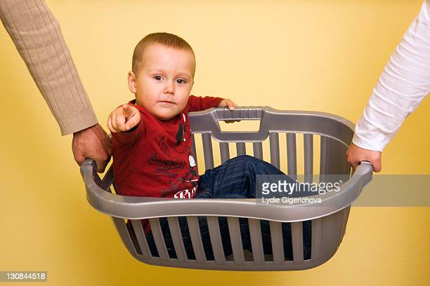 Boy, 2 years, being carried in a laundry basket