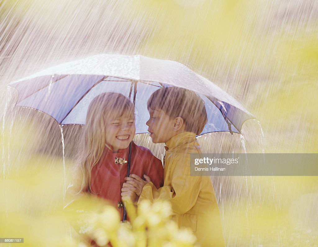 boy about to kiss under umbrella during rainstorm stock photo