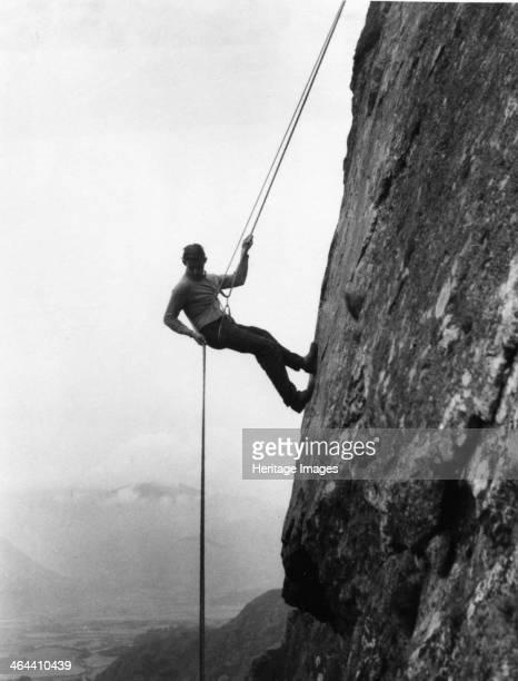 Boy abseiling down rock face Outward Bound School Eskdale Cumbria 1950