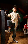 Boy (8-10) acting as lumberjack on stage, one foot on tree stump