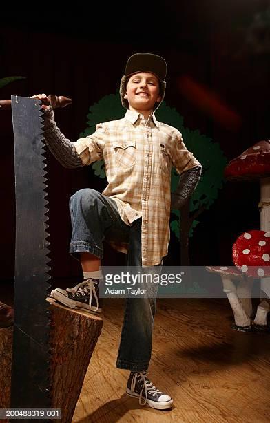 Boy (8-10) acting as lumberjack on stage, one foot on tree stump