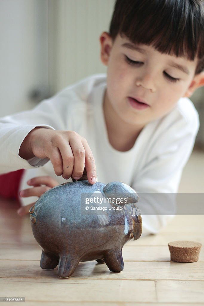 Boy adding coins to his piggy bank as savings