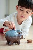 Boy adding coins to his piggy bank as savings