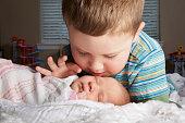 Boy admiring newborn sibling on bed