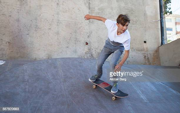 Boy, aged 14, riding a skateboard