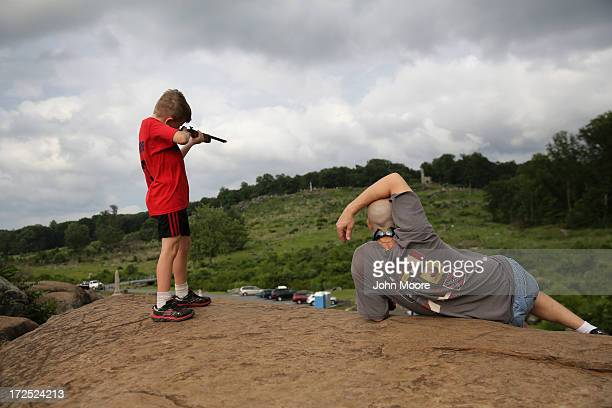 A boy aims his toy gun from Devil's Den to Little Round Top site of heavy Civil War fighting on July 2 2013 in Gettysburg Pennsylvania on the 150th...