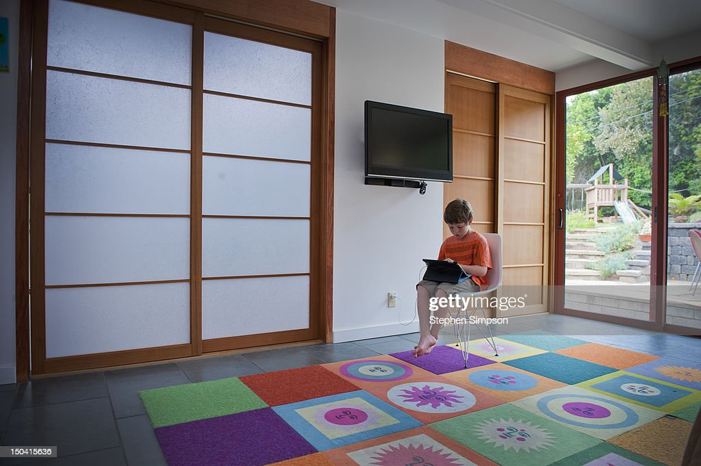 boy, 7, alone with laptop in a large room : Stock Photo
