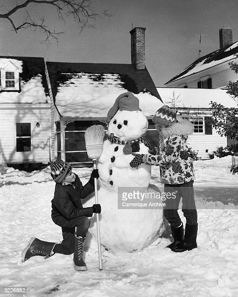 A boy and a girl building a snowman in their front yard The snowman has a stocking cap a pipe a scarf and lumps of coal for its face and buttons