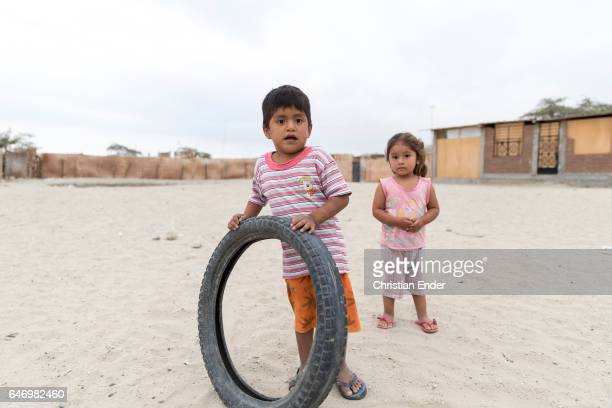 A boy and a girl in a slum wearing pink clothes The boy is holding a rubber wheel on February 06 2015 in Piura Peru