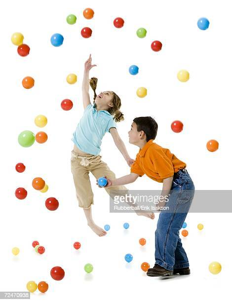 A boy and a girl playing with colorful balls
