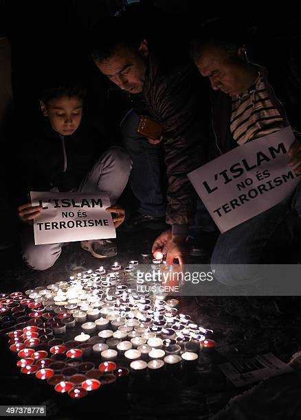 A boy and a man hold posters reading 'Islam is not terrorism' near candles in the colours of the French national flag during a demonstration called...