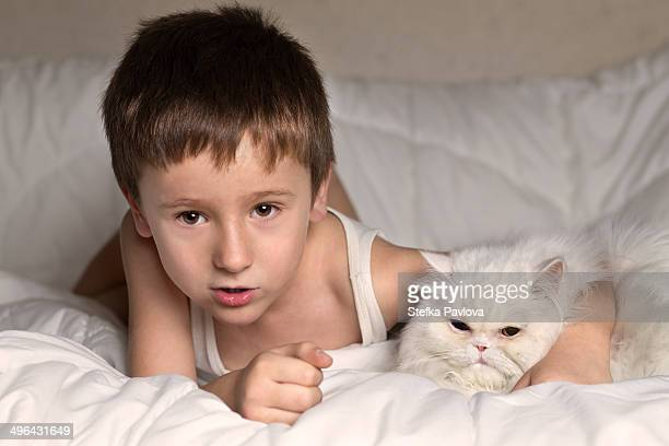 Boy and a white Persian cat in bed