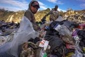 A boy and a young man scavenge for food clothes and other items in a landfill which is prone to fires and other accidents January 18 2014 in...