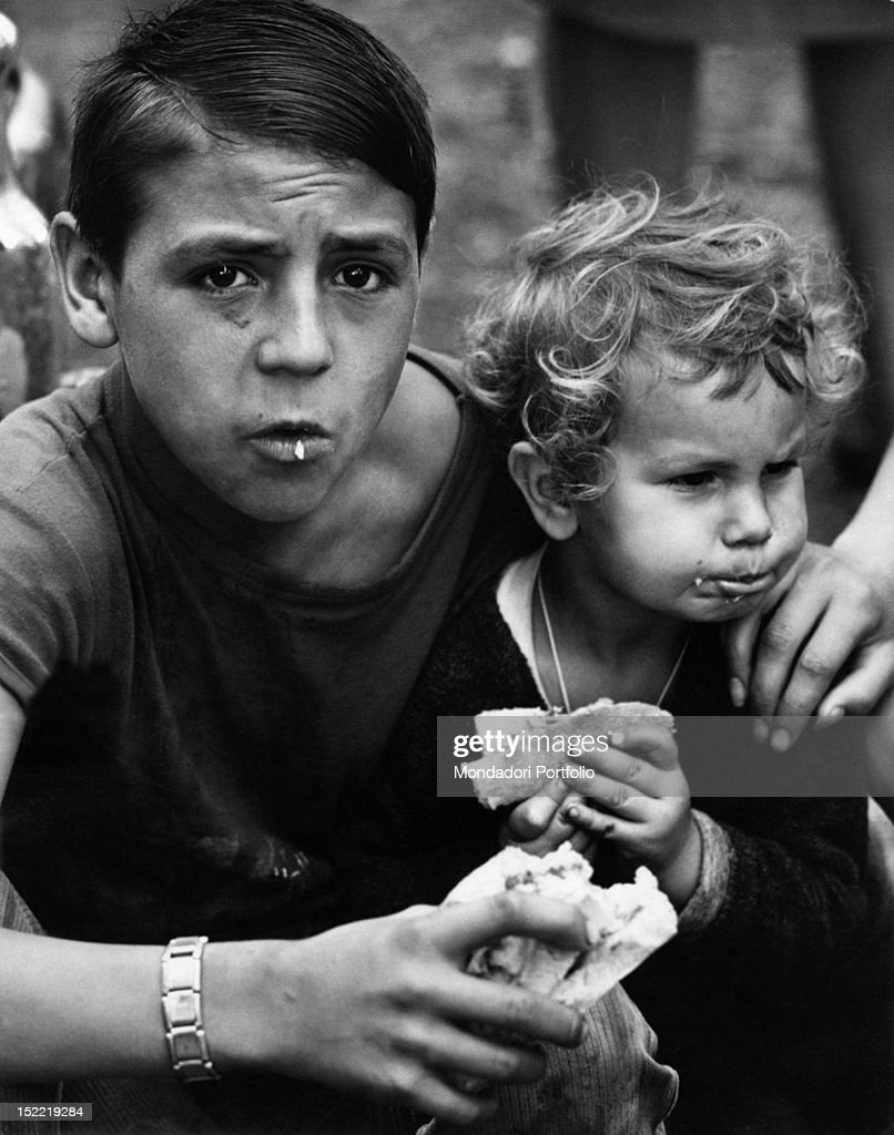 gipsy child A boy and a younger blond-hair child are eating a sandwich at the gypsy