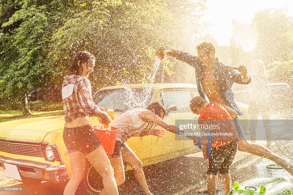 Boy and adult friends drenching each other whilst washing vintage car