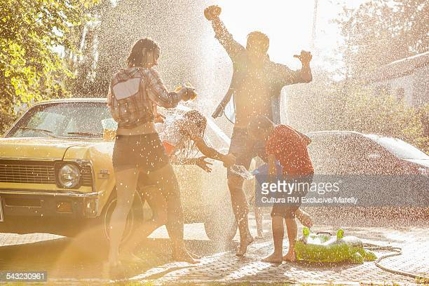 Boy and adult friends splashing each other whilst washing car