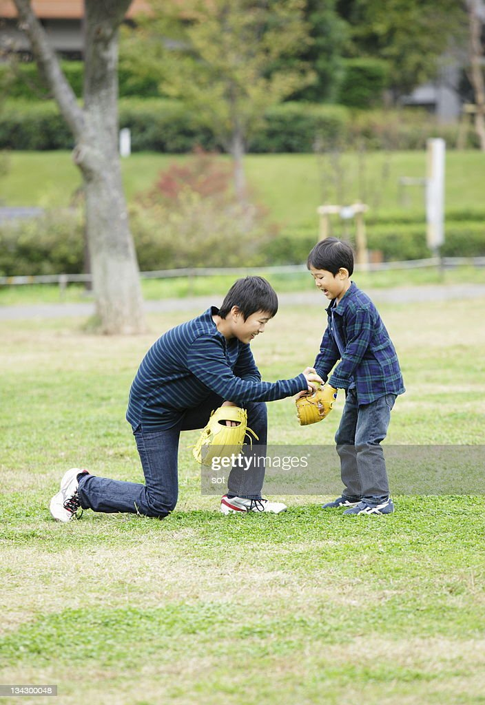 Boy and baby boy playing catch in park : Stock Photo