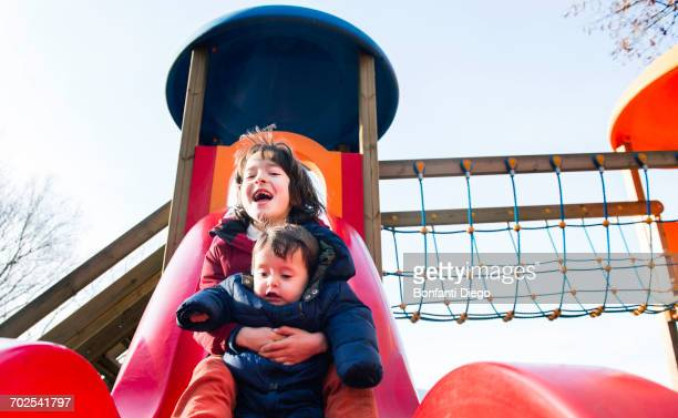Boy and baby brother sliding down playground slide