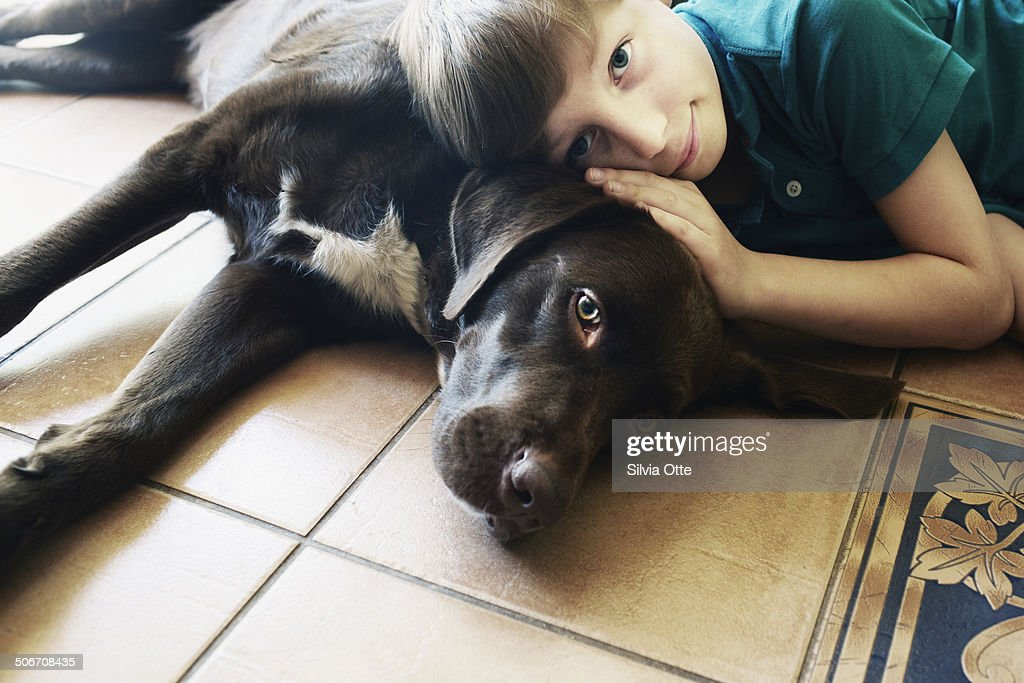 Boy and dog cuddling on floor together