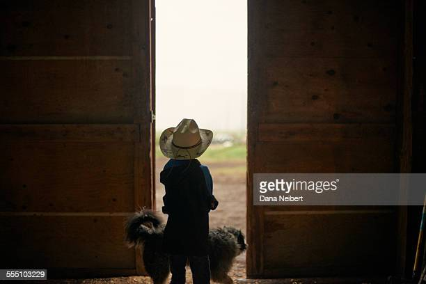 Boy and dog looking out barn doors