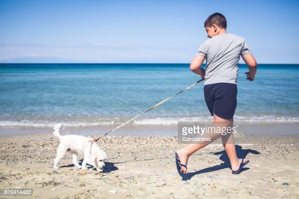 Boy and dog running along a sandy beach on a summer day