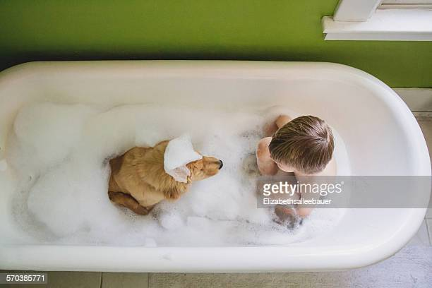 Boy and dog sitting in bathtub