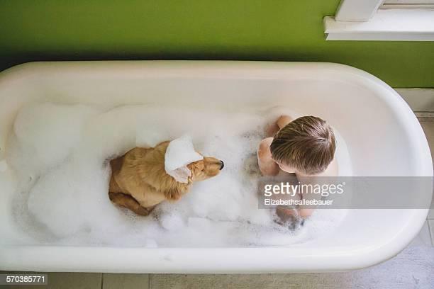 Boy and dog sitting in bathtub