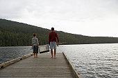 Boy (9-11 years) and father carrying fishing tackle on jetty, rear view