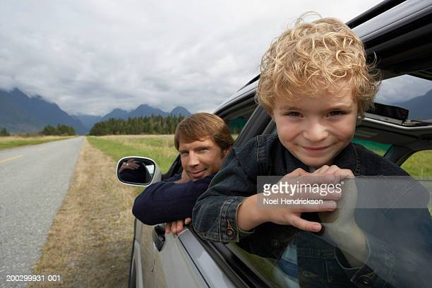 Boy (5-7 years) and father leaning out of car windows, smiling, portrait, close-up