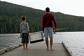 Boy (5-7 years) and father on jetty, carrying fishing tackle, rear view