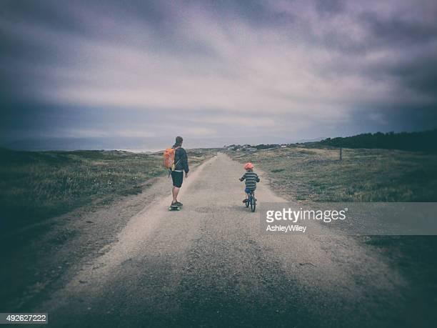 Petit garçon et son père rider sur un chemin de terre sur vélo