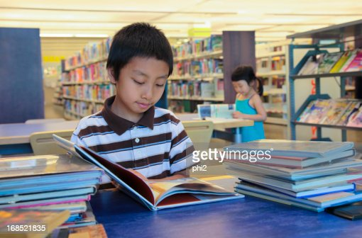 Boy and Girl Asian Kids Reading Books in A Library