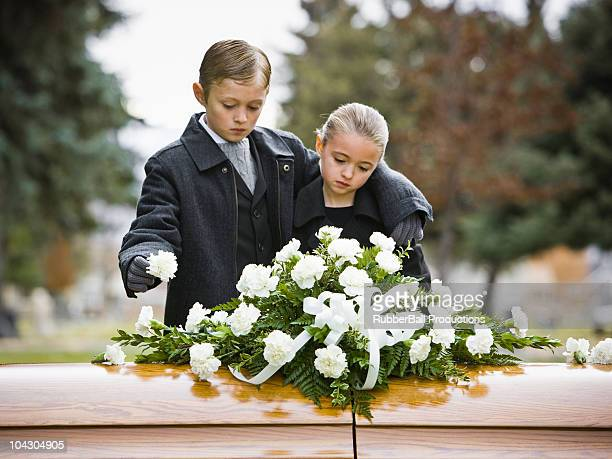 boy and girl at a funeral standing next to a coffin