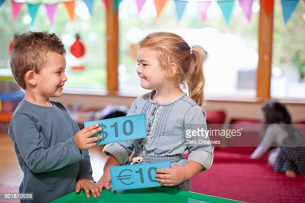 Boy and girl counting euro currency at nursery school