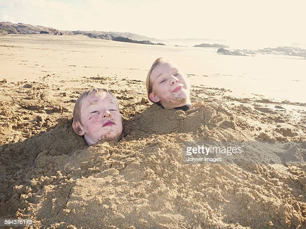 Boy and girl covered by sand