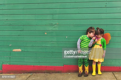 Boy and girl dressed up as a caterpillar and butterfly smelling flowers
