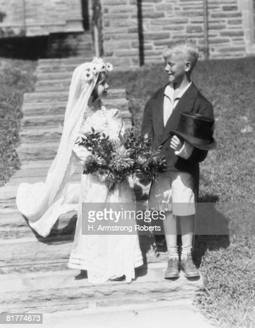 Boy and girl dressed up as bride and groom, outdoors on steps. : Stock Photo