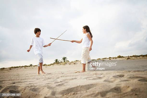 Boy and girl (8-10) duelling with pretend swords, low angle view