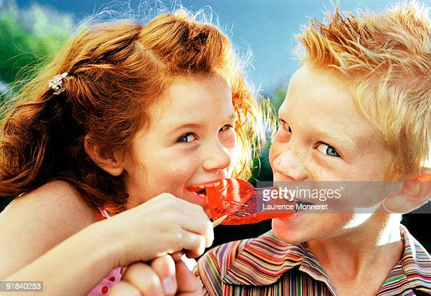 Boy and girl eating lollipop
