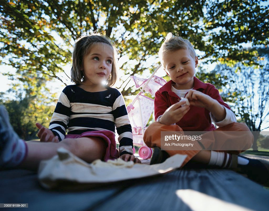Boy and girl (4-7) eating on picnic table in park (wide angle