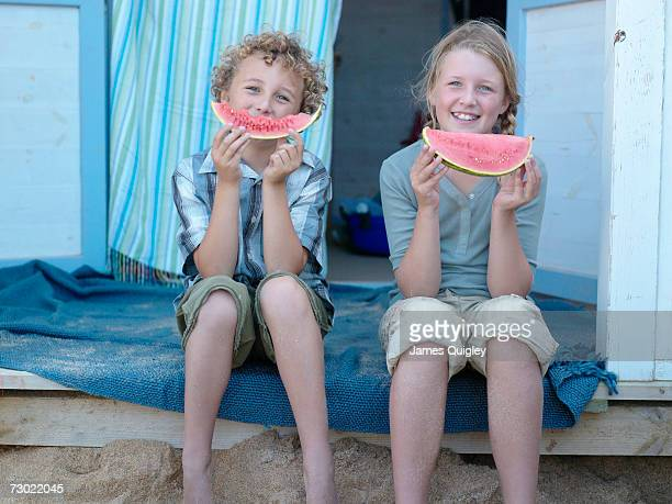 Boy (7-9) and girl (8-10) eating watermelon on porch