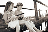 Boy and girl fishing from a dock