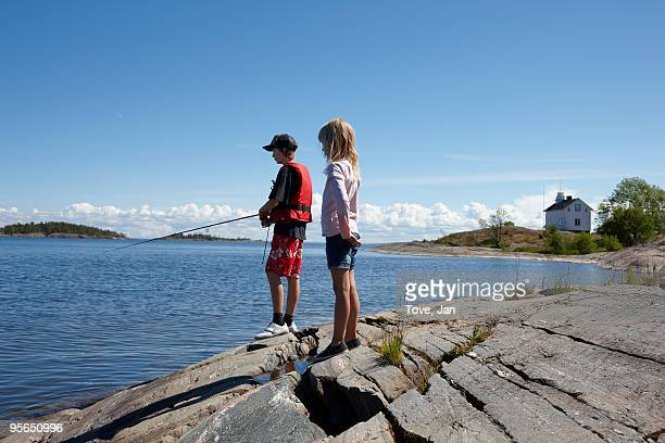 Boy and girl fishing, Sweden.