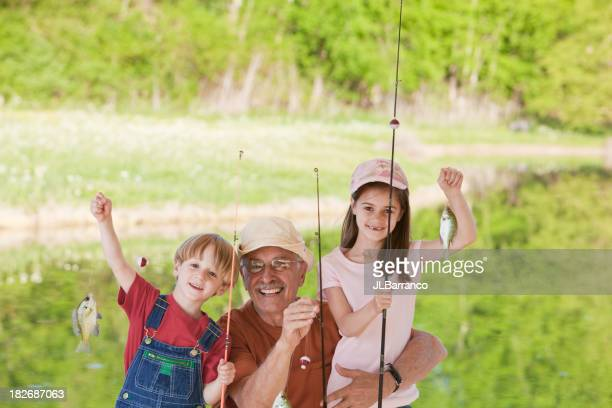 Boy and girl fishing with grandfather