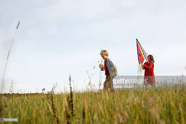Boy (10-12) and girl (7-9) flying kite