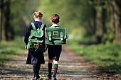 Boy (6-7) and girl (8-9) going  school through forest, rear view