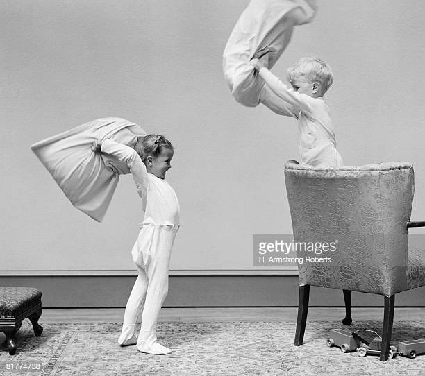 Boy and girl having a pillow fight, boy standing on chair swinging pillow, girl on floor.