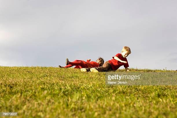Boy (10-12) and girl (7-9) having fun in meadow